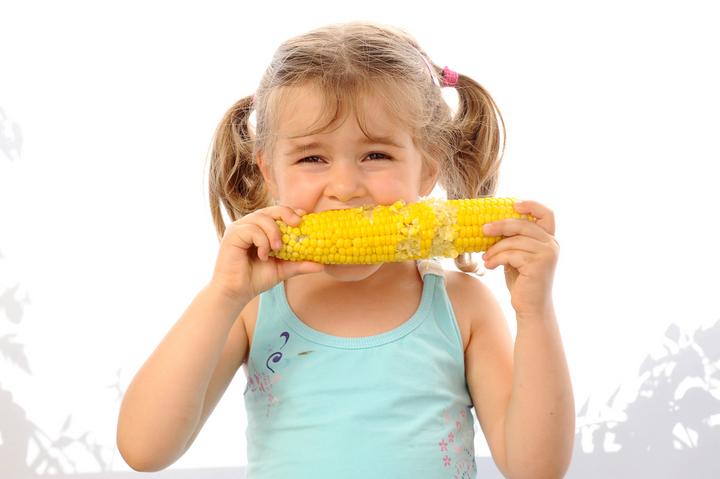 Девочка кушает початок