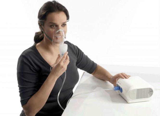 Женщина дышит в небулайзер
